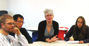 A woman sitting at a table explaining soemthing with her hands