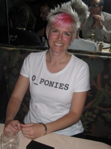 A smiling woman with pink hair wearing a t shirt with the word