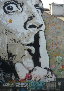 Mural of a man's face holding his finger to his lips in a