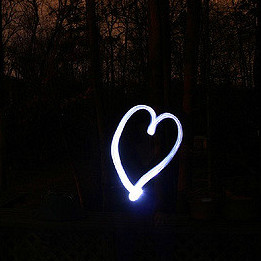 A light painting of a heart on a background of a wood at sunset