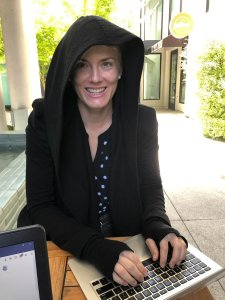 A woman wearing a dramatic black hooded jacket typing on a laptop