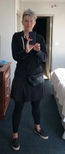 A woman wearing all black with a fanny pack